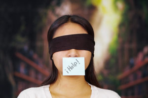 Young brunette woman wearing white sweater, blindfolded with black textile, paper note covering mouth reading help, facing camera, hostage concept.